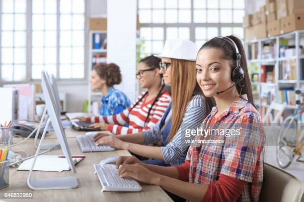 Smiling young women using computers in modern call center
