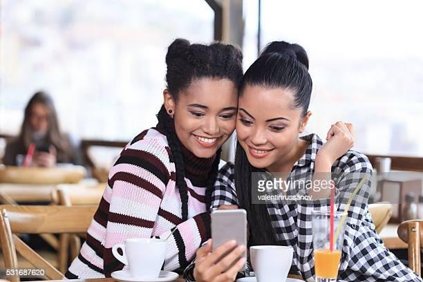 Sorridente Jovem mulher usando o telefone em um restaurante