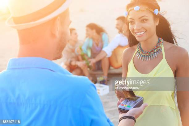 Smiling yYoung woman using credit card on beach
