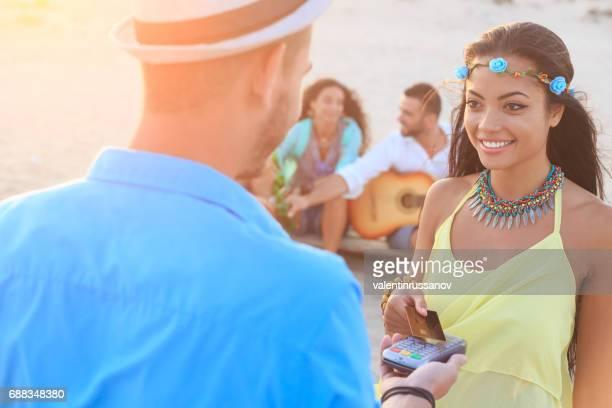 Sonriente mujer yYoung usando tarjeta de crédito en la playa