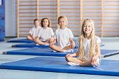 Smilling girl sitting on blue mat during sport gymnastics classes