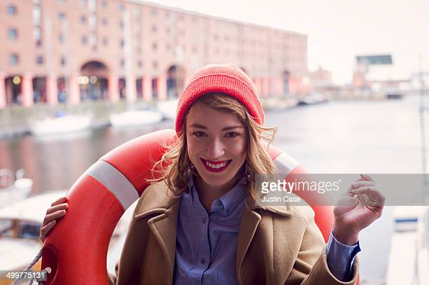 smily woman carrying a life belt in a harbor
