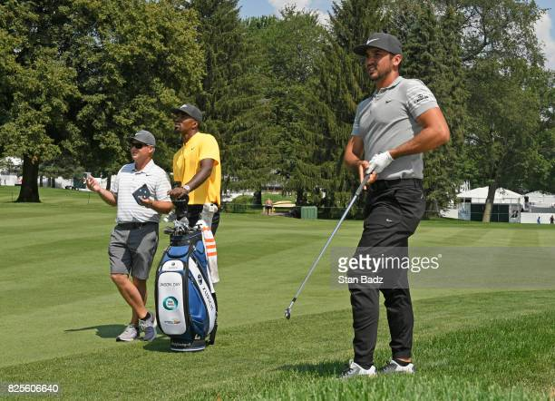 R Smith of Cleveland Cavaliers and Colin Swatton Jason Day's caddie watch as Day hits a shot during practice of the World Golf...