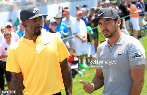 R Smith of the Cleveland Cavaliers and Jason Day of Australia speak on the 18th green during a preview day of the World Golf Championships...
