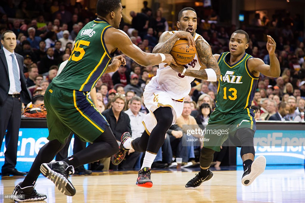 R Smith of the Cleveland Cavaliers drives through Derrick Favors and Elijah Millsap of the Utah Jazz during the second half at Quicken Loans Arena on...