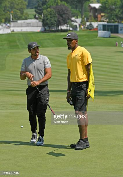 R Smith of the Cleveland Cavaliers spends some time with Jason Day on the course during practice of the World Golf ChampionshipsBridgestone...