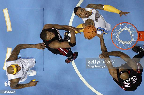 R Smith of the Denver Nuggets puts up a shot between Chris Bosh and Eric Dampier of the Miami Heat as Al Harrington of the Nuggets follows the play...