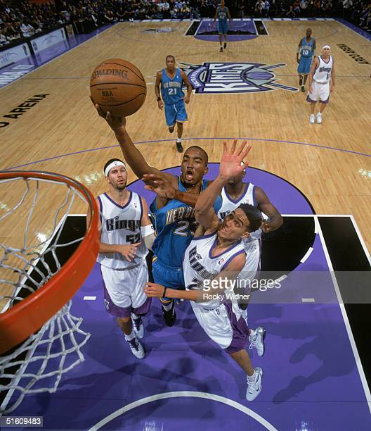 R Smith of the New Orleans Hornets drives to the basket for a layup between Brad Miller and Kevin Martin of the Sacramento Kings during a preseason...