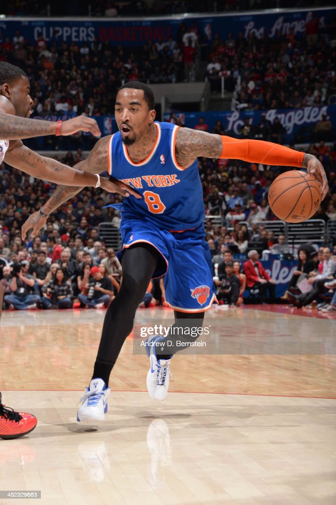 J.R. Smith #8 of the New York Knicks dribbles against Reggie Bullock #25 of the Los Angeles Clippers at Staples Center on November 27, 2013 in Los Angeles, California.