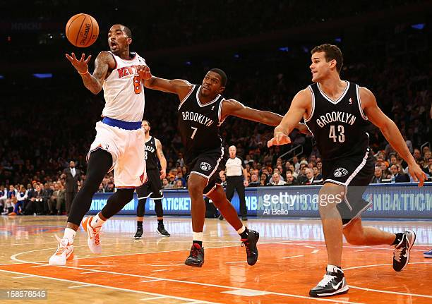 R Smith of the New York Knicks grabs a rebound as Joe Johnson and Gerald Wallace of the Brooklyn Nets defend during their game at Madison Square...
