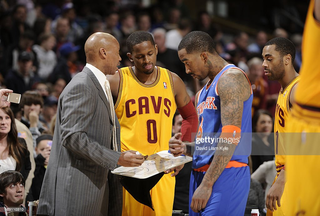 J.R. Smith #8 of the New York Knicks jokingly joins in the huddle between Cleveland Cavaliers' head coach Byron Scott and C.J. Miles #0 during a break in the action at The Quicken Loans Arena on March 4, 2013 in Cleveland, Ohio.