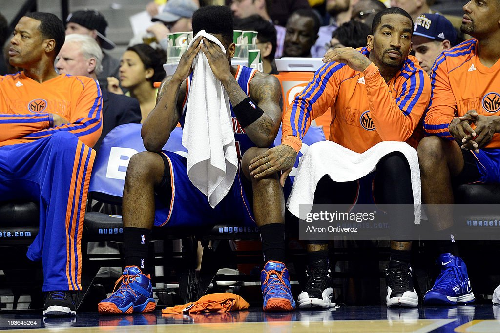 J.R. Smith (8) of the New York Knicks pats the knee of Iman Shumpert (21) of the New York Knicks as he covers his face during the second half of of the Nuggets' win. The Denver Nuggets play the New York Knicks at the Pepsi Center.