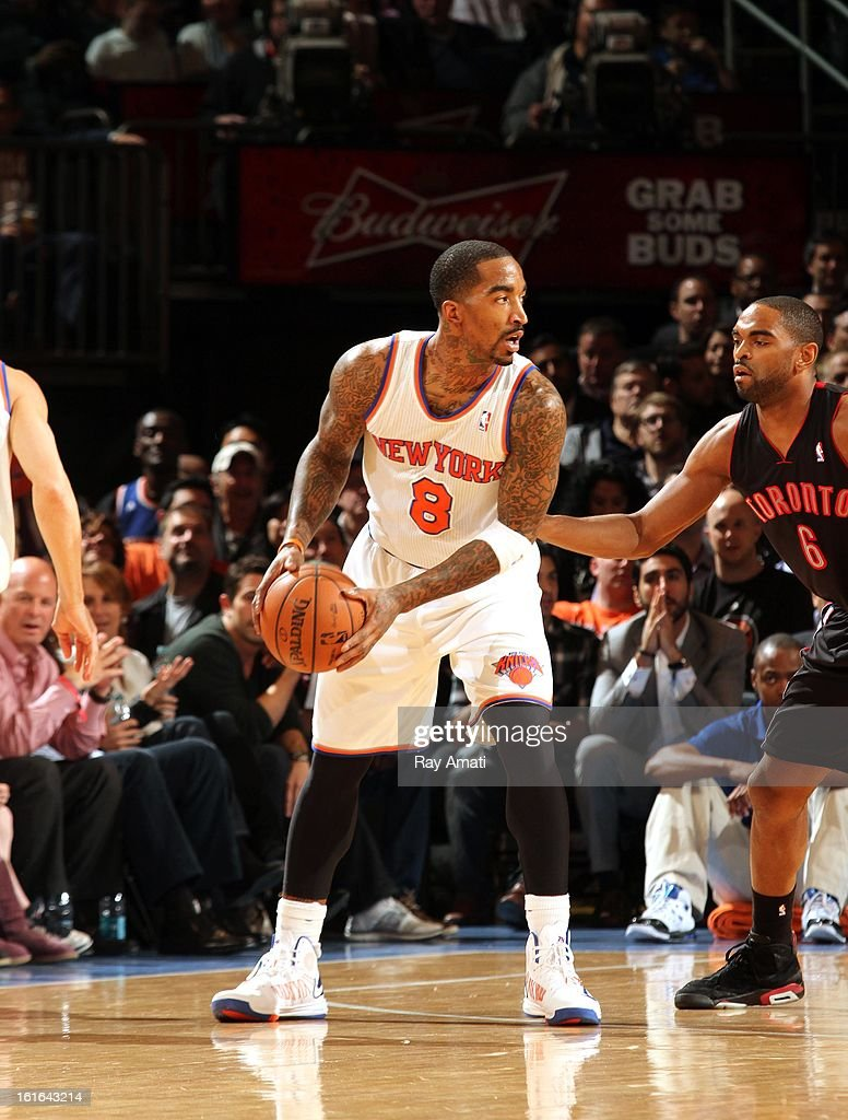 J.R. Smith #8 of the New York Knicks protects the ball against Alan Anderson #6 of the Toronto Raptors on February 13, 2013 at Madison Square Garden in New York City.