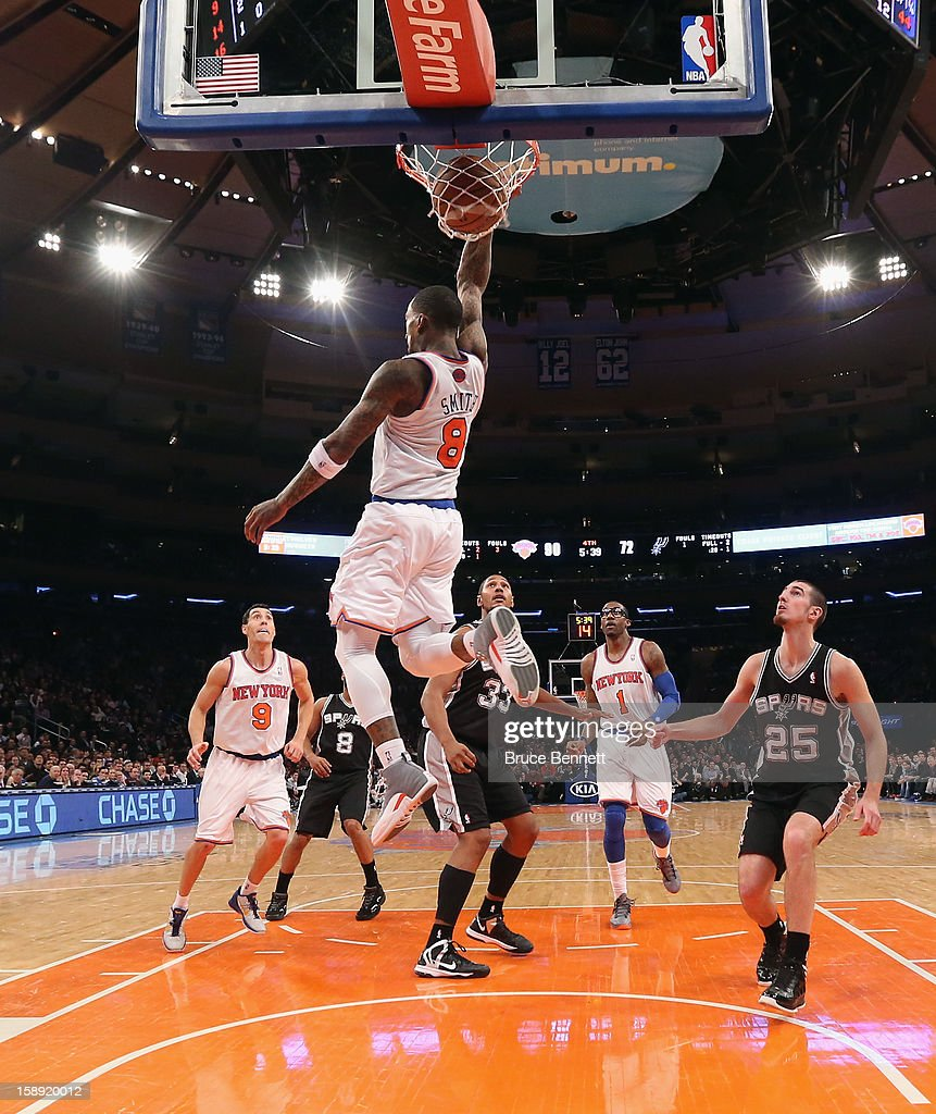 J.R. Smith #8 of the New York Knicks scores a basket behind his head late in the fourth quarter against the San Antonio Spurs at Madison Square Garden on January 3, 2013 in New York City.
