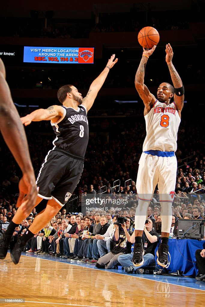 J.R. Smith #8 of the New York Knicks shoots a three-pointer against Deron Williams #8 of the Brooklyn Nets on January 21, 2013 at Madison Square Garden in New York City.
