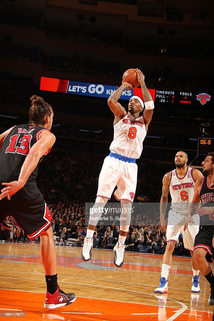 J.R. Smith #8 of the New York Knicks shoots against Joakim Noah #13 of the Chicago Bulls on January 11, 2013 at Madison Square Garden in New York City.