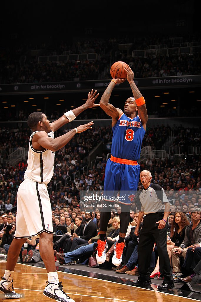 J.R. Smith #8 of the New York Knicks shoots against Joe Johnson #7 of the Brooklyn Nets on December 11, 2012 at the Barclays Center in the Brooklyn borough of New York City.