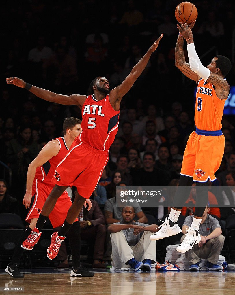 J.R. Smith #8 of the New York Knicks takes a shot over DeMarre Carroll #5 of the Atlanta Hawks during the first quarter at Madison Square Garden on November 16, 2013 in New York City.