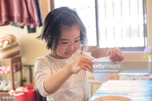 Smling Japanese Girl Examining Slime Science Experiment at Home