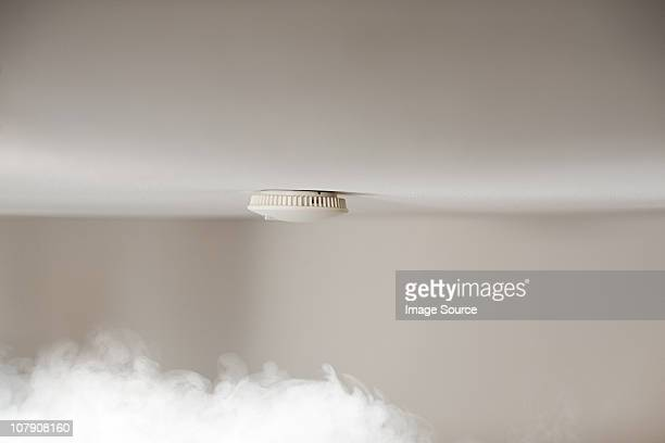 Smoke alarm on ceiling with smoke