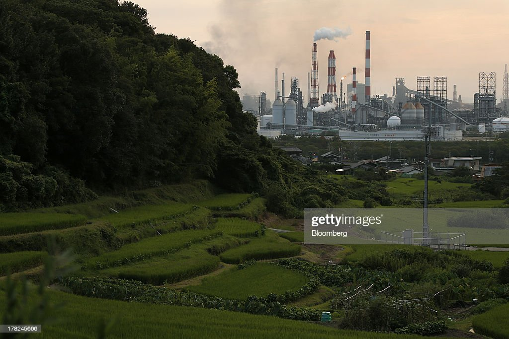 Smoke and a flame rise from stacks at plants beyond fields and residential houses in the Mizushima coastal industrial complex in Kurashiki, Okayama Prefecture, Japan, on Monday, Aug. 26, 2013. Japan's top listed companies doubled earnings last quarter from a year earlier, exceeding already high forecasts and generating support for the economic recovery effort of Prime Minister Shinzo Abe. Photographer: Kiyoshi Ota/Bloomberg via Getty Images