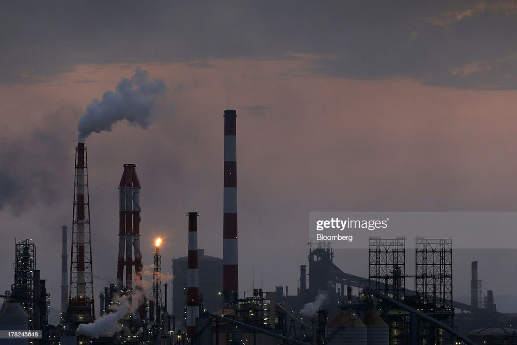 Smoke and a flame rise from stacks at plants illuminated at dusk in the Mizushima coastal industrial complex in Kurashiki, Okayama Prefecture, Japan, on Monday, Aug. 26, 2013. Japan's top listed companies doubled earnings last quarter from a year earlier, exceeding already high forecasts and generating support for the economic recovery effort of Prime Minister Shinzo Abe. Photographer: Kiyoshi Ota/Bloomberg via Getty Images