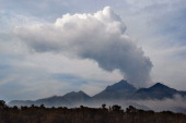 Smoke and ash rise from Mount Kelud as seen from Malang in East Java on February 18 2014 following the February 13 eruption that killed four people...