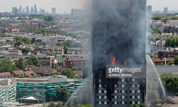 TOPSHOT Smoke and flames billows from Grenfell Tower as firefighters attempt to control a blaze at a residential block of flats on June 14 2017 in...