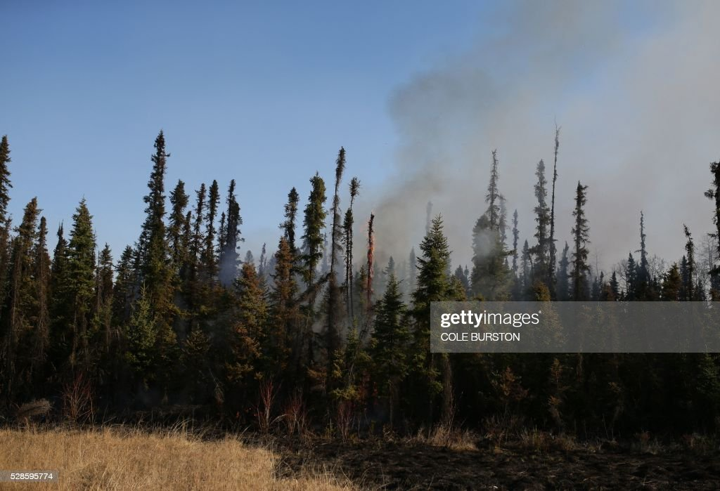 Smoke and flames can be seen along the highway near Fort McMurray, Alberta on May 6, 2016. Canadian police led convoys of cars through the burning ghost town of Fort McMurray Friday in a risky operation to get people to safety far to the south.In the latest chapter of the drama triggered by monster fires in Alberta's oil sands region, the convoys of 50 cars at a time are driving through the city at about 50-60 kilometers per hour (30-40 miles per hour) TV footage showed. / AFP / Cole Burston