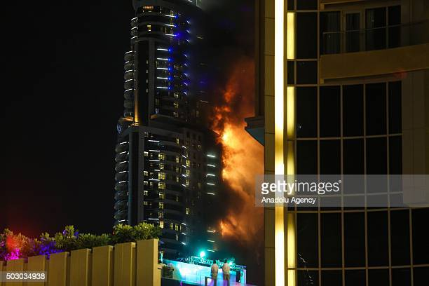 Smoke and flames pour from 63story skyscraper near the world's tallest tower 'Burj Khalifa' after a huge fire erupted in Dubai United Arab Emirates...