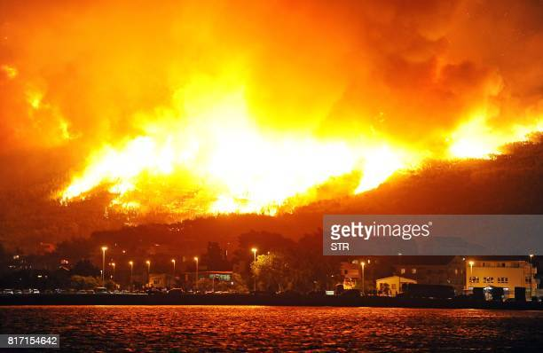 Smoke and flames rise from a fire in the village of Podstrana near the Adriatic coastal town of Split early on July 18 2017 Montenegro asked on July...