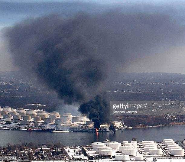 Smoke and flames rise from an explosion at an oil storage refinery February 21 2003 in the Staten Island borough of New York Initial reports say that...