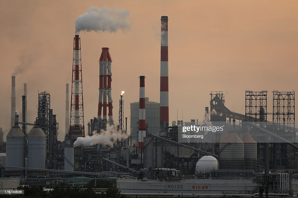 Smoke and flames rise from stacks at plants at dusk in the Mizushima coastal industrial complex in Kurashiki, Okayama Prefecture, Japan, on Monday, Aug. 26, 2013. Japan's top listed companies doubled earnings last quarter from a year earlier, exceeding already high forecasts and generating support for the economic recovery effort of Prime Minister Shinzo Abe. Photographer: Kiyoshi Ota/Bloomberg via Getty Images