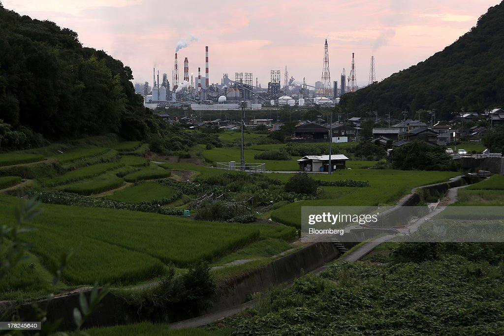 Smoke and flames rise from stacks at plants beyond fields and residential houses at dusk in the Mizushima coastal industrial complex in Kurashiki, Okayama Prefecture, Japan, on Monday, Aug. 26, 2013. Japan's top listed companies doubled earnings last quarter from a year earlier, exceeding already high forecasts and generating support for the economic recovery effort of Prime Minister Shinzo Abe. Photographer: Kiyoshi Ota/Bloomberg via Getty Images