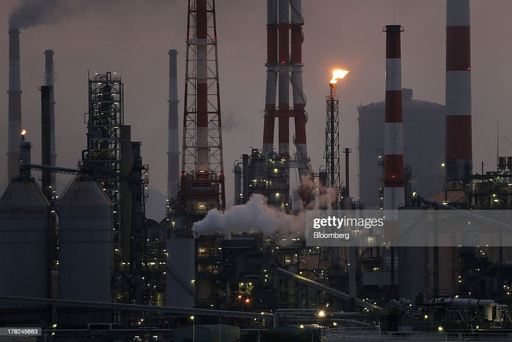 Smoke and flames rise from stacks at plants illuminated at dusk in the Mizushima coastal industrial complex in Kurashiki, Okayama Prefecture, Japan, on Monday, Aug. 26, 2013. Japan's top listed companies doubled earnings last quarter from a year earlier, exceeding already high forecasts and generating support for the economic recovery effort of Prime Minister Shinzo Abe. Photographer: Kiyoshi Ota/Bloomberg via Getty Images