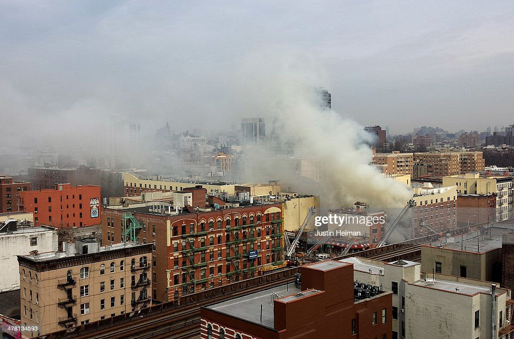 Smoke and steam rises from the scene as firefighters from the Fire Department of New York (FDNY) respond to a 5-alarm fire and building collapse at 1646 Park Ave in the Harlem neighborhood of Manhattan March 12, 2014 in New York City. Reports of an explosion were heard before the collapse of two multiple-dwelling buildings that left at least 11 injured.