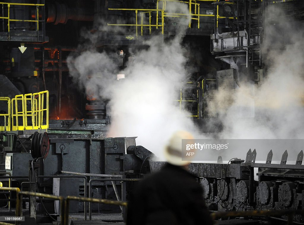 Smoke arises as a steel slab passes on a hot mill train, on January 9, 2013 in Florange, eastern France. ArcelorMittal, run by steel tycoon Lakshmi Mittal, had said it will shut down two furnaces at Florange that are no longer used if a buyer for them cannot be found.