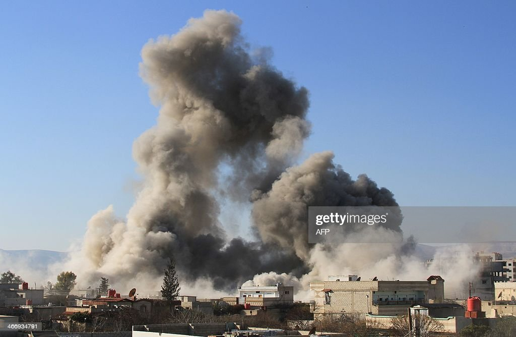 Smoke ascends after a Syrian military helicopter allegedly dropped a barrel bomb over the city of Daraya southwest of the capital Damascus on...