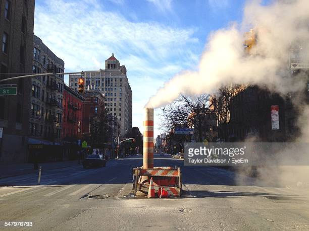 Smoke At Construction Site On Street Amidst Buildings In City