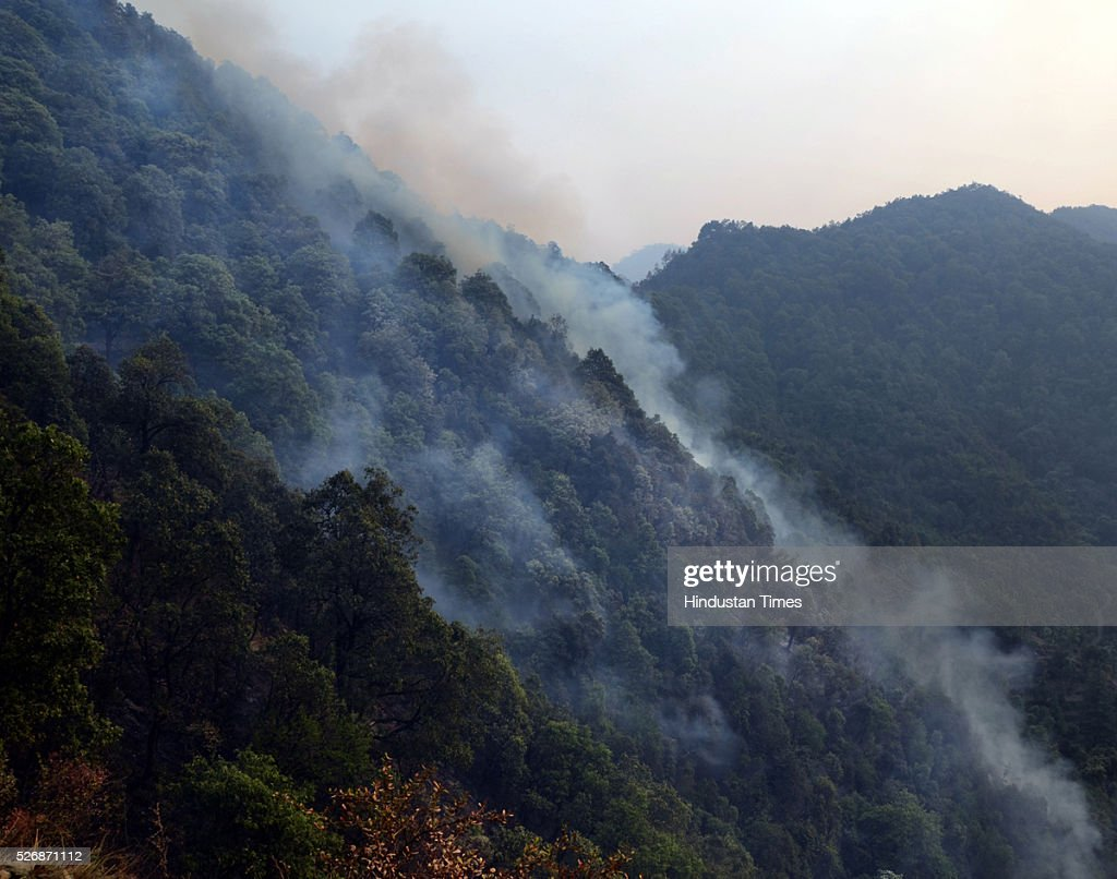 Smoke belching out of the jungles of Mandakhal, on May 1, 2016 in Uttarakhand, India. Two Indian Air Force (IAF) choppers began spraying water over the burning forests in Uttarakhand on Sunday morning. Major forest fires raged across Uttarakhand even as two Indian Air Force (IAF) choppers have begun spraying water to extinguish the flames. Presently, some 5,000 workers -- including 3,000 daily wagers -- are engaged in putting out the fire. More than 2300 hectares of forest have been gutted in the fire since it was first reported in February this year. Dry winters and soaring temperatures are blamed for the fire that has affected all 13 districts of the state.
