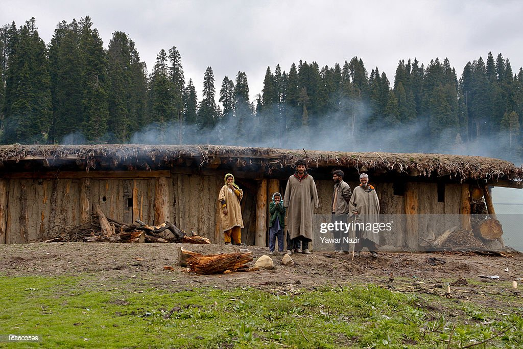 Smoke billowing from a mud-hut of a Kashmiri nomad family (standing in front) in Doodhpathri Valley, on May 12, 2013 , 50 kms (31 milies) west of Srinagar, the summer capital of Indian administered Kashmir, India. Despite its lush green meadows, natural water springs and gushing streams, Doodhpathri remains largely unknown to tourists visiting Kashmir, mainly due to poor roads conditions. Locals say that if authorities pay attention towards developing infrastructure and other facilities, Doodhpathri (literally Valley of milk) could turn out to be a major tourist destination just as other well-known resorts like Gulmarg and Pahalgam.