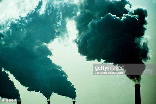 Smoke billowing from industrial smoke stacks