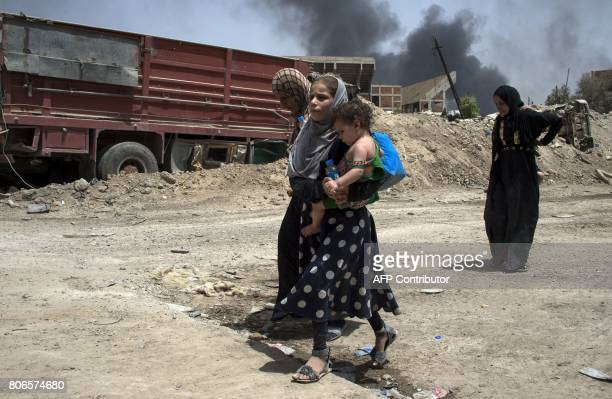 Smoke billows as an Iraqi woman and children flee the Old City of Mosul on July 3 during the government forces' ongoing offensive to retake the city...