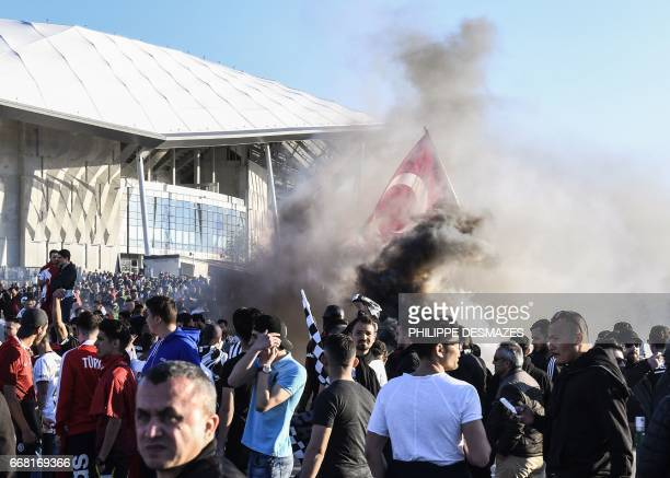 Smoke billows as Besiktas supporters gather outside the Parc Olympique Lyonnais stadium while clashes erupted with French antiriot Gendarmes and...