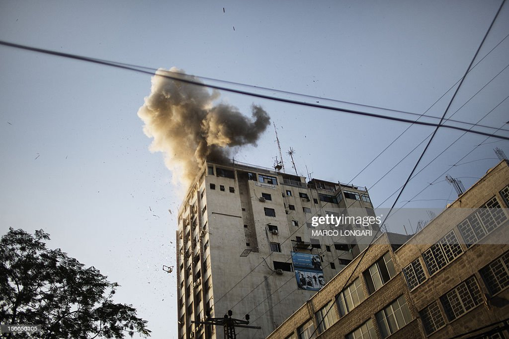 Smoke billows as debris flies from the explosion at the local Al-Aqsa TV station in Gaza City on November 18, 2012 after it was attacked during an Israeli airstrike. An Israeli air strike hit a Gaza City media building on November 18, injuring at least six journalists, as a separate raid in northern Gaza killed two people, Palestinian medical sources said. AFP PHOTO / MARCO LONGARI