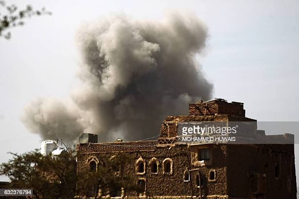 Smoke billows behind a building following a reported air strike by the Saudiled coalition in the Yemeni capital Sanaa on January 22 2017 / AFP /...