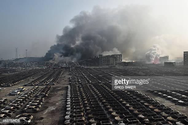 Smoke billows behind rows of burnt out cars at the site of a series of explosions in Tianjin northern China on August 13 2015 A series of massive...