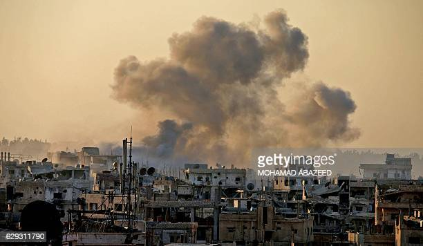 TOPSHOT Smoke billows during reported shelling by Syrian government forces in the rebelheld area of Daraa in southern Syria on December 12 2016 / AFP...