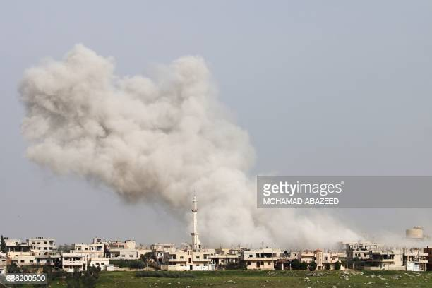 TOPSHOT Smoke billows following a reported air strike on a rebelheld area in the southern Syrian city of Daraa on April 8 2017 / AFP PHOTO / Mohamad...