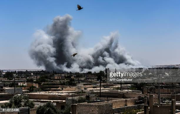 TOPSHOT Smoke billows following an airstrike on the western frontline of Raqa on July 15 during an offensive by the Syrian Democratic Forces an...